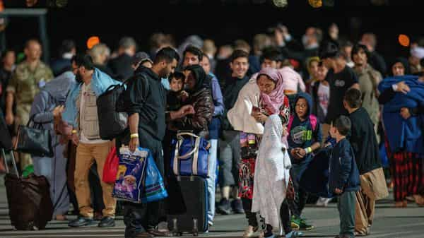 Families evacuated from Kabul, Afghanistan, walk away from a U.S air force plane after arriving at Kosovo