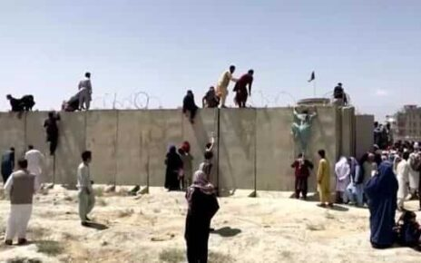People climb a barbed wire wall to enter the airport in Kabul, Afghanistan August 16, 2021, in this still image taken from a video. (REUTERS)