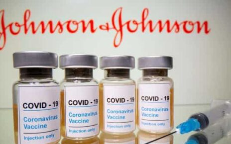 Vials with a sticker reading, 'COVID-19 / Coronavirus vaccine / Injection only' and a medical syringe are seen in front of a displayed Johnson & Johnson logo in this illustration (REUTERS)