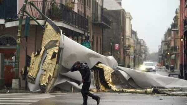 A man passes by a section of roof that was blown off of a building in the French Quarter by Hurricane Ida winds in New Orleans (Photo: AP)